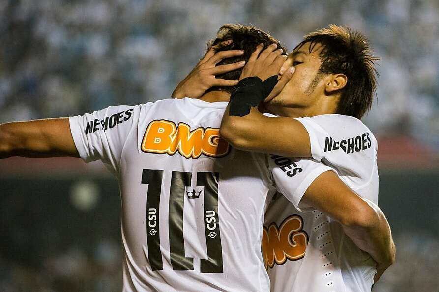 Santos's footballer Neymar (R) speaks to teammate Ganso before  a free-kick against Guarani during t