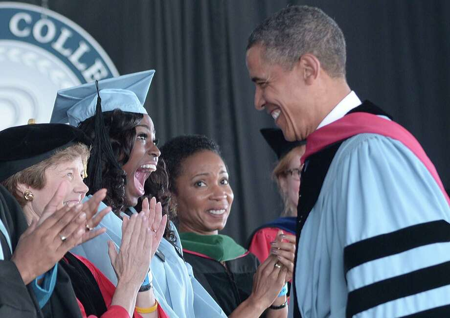 President Barack Obama greets graduate Britney Wilson on Monday before making the commencement address at Barnard College. He did not directly criticize Mitt Romney at the speech. Photo: MANDEL NGAN / AFP