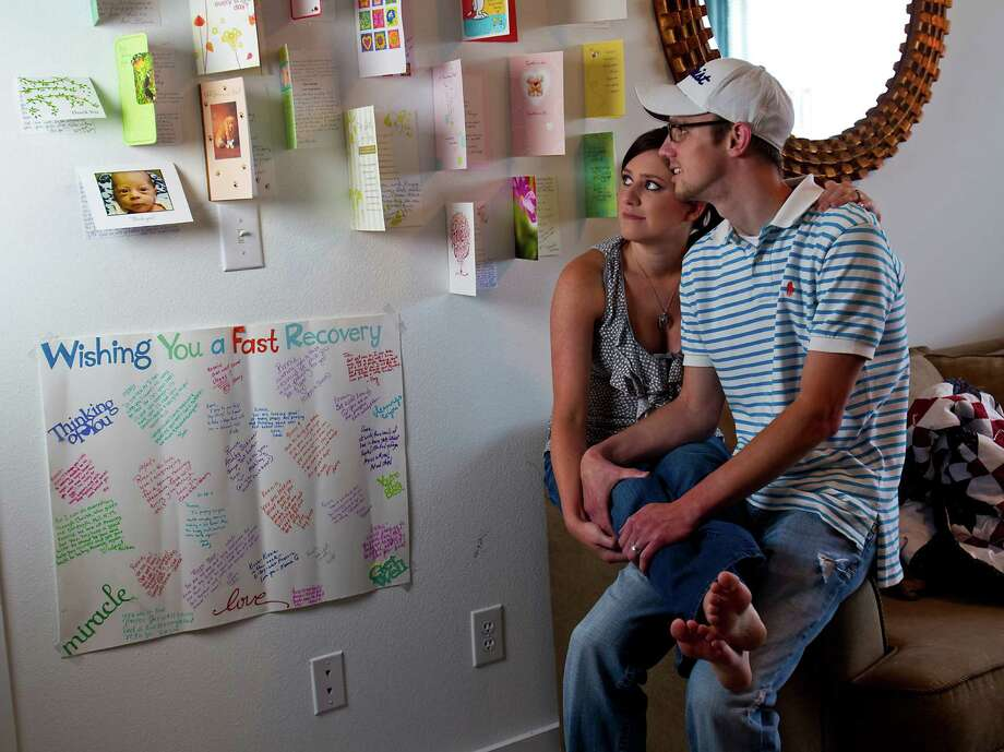 "Dayna Window and her husband Ronnie Reitz look at ""get well"" cards and notes on the wall of their home, Sunday in Houston. Photo: Karen Warren / © 2012  Houston Chronicle"