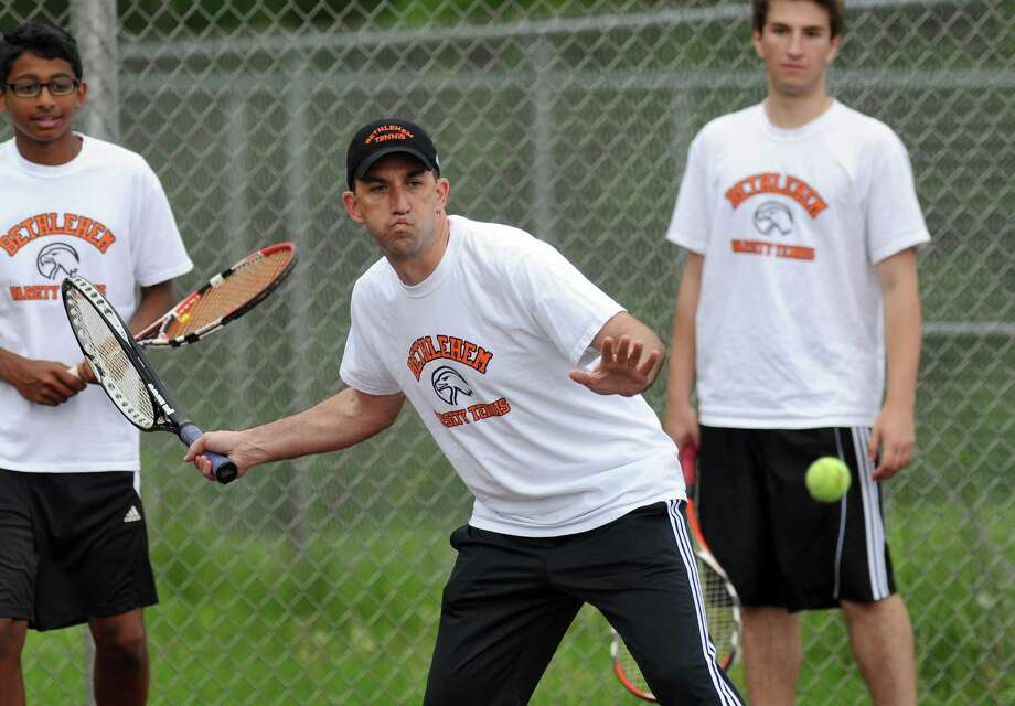 Bethlehem High School boys tennis coach Stephen Smith practices with his team as they awaited their opening round opponent in the Section II tournament, at the school on Monday May 14, 2012 in Delmar, NY.  (Philip Kamrass / Times Union ) Photo: Philip Kamrass / 00017663A