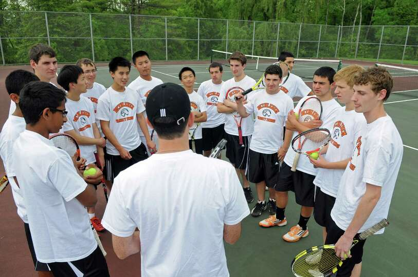 Bethlehem High School boys tennis coach Stephen Smith, back to camera, talks to his players during p