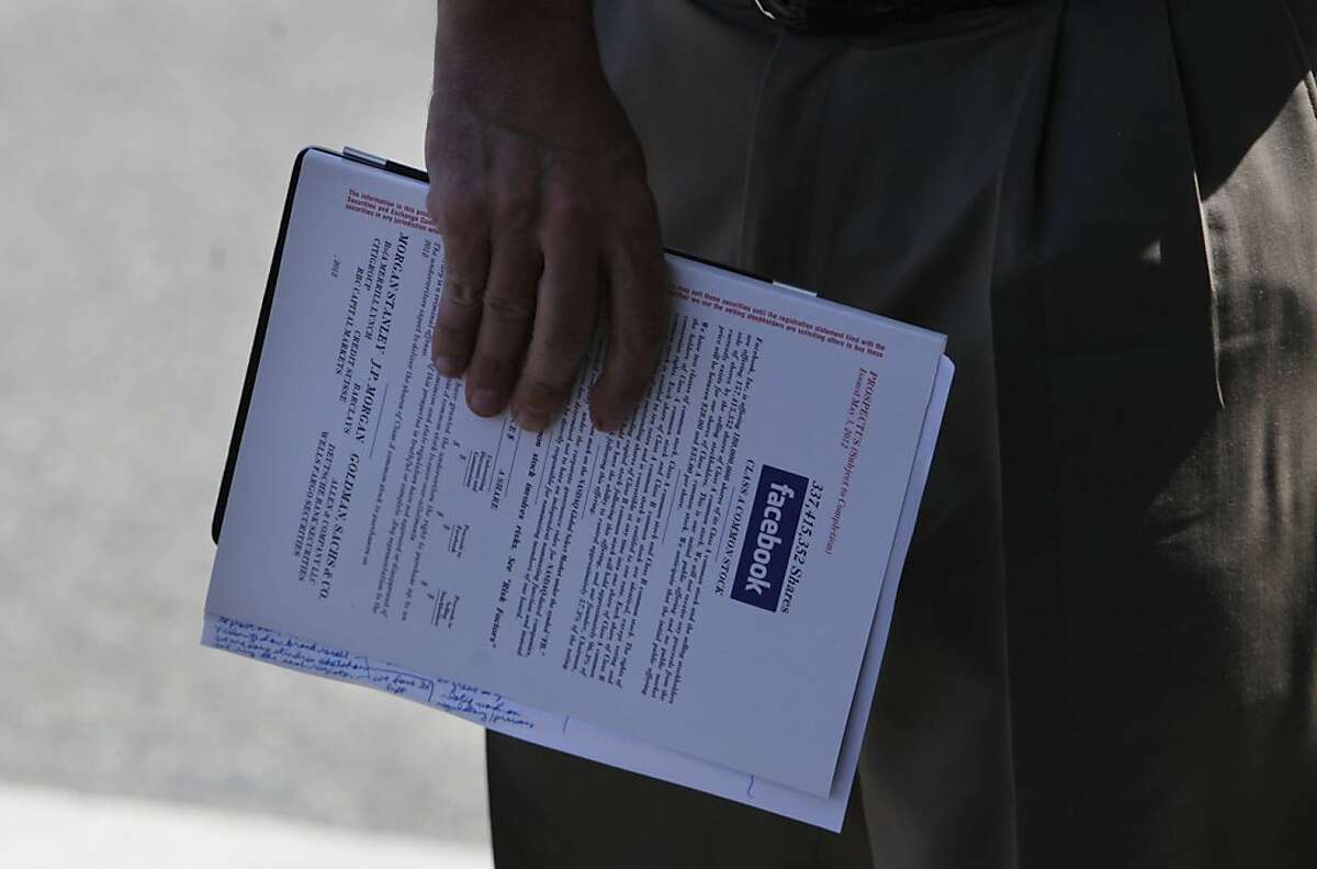 A potential investor carries a Facebook prospectus as he leaves the Crowne Plaza Hotel in Palo Alto on Friday, May 11, 2012 in Palo Alto, Calif.