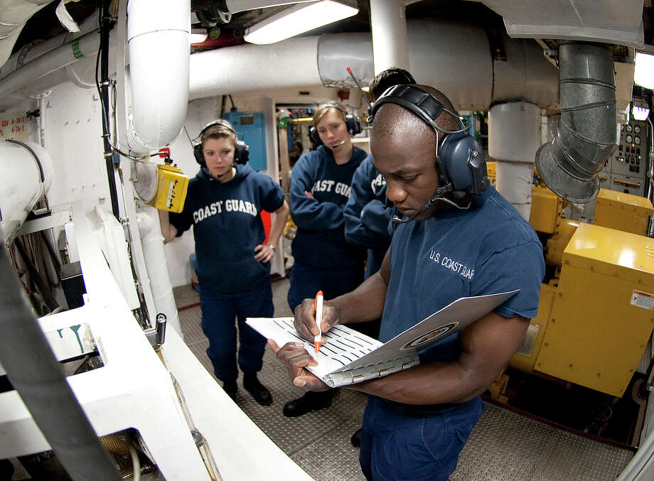 Orlando Morel reviews a logbook in the generator room of the Coast Guard Cutter Eagle. On Wednesday, he will graduate from the Coast Guard Academy. Photo: NyxoLyno Cangemi / Public Domain - U.S. COAST GUARD