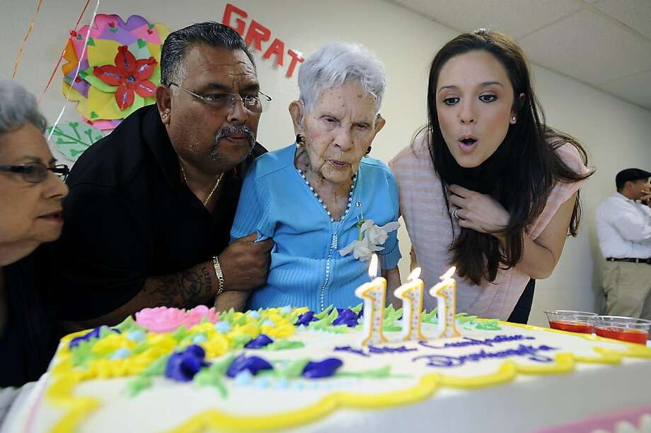 Grandson Michael J. Sanchez(L) and great granddaughter Erika Latour(R) help Dominga blow out the candles on her birthday cake. Dominga Velasco turned 111 years old at the Posada De Colores nursing home in Oakland, CA Monday May 14th, 2012 Photo: Michael Short, Special To The Chronicle
