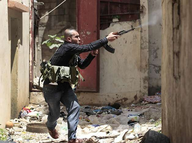 A Sunni gunman fires during clashes, in the northern port city of Tripoli, Lebanon, Monday May 14, 2012. Street battles pitting Lebanese Sunnis who generally support the Syrian uprising, against Alawite supporters of Assad's regime killed at least one person Monday, raising the death toll to four since Sunday. The clashes began Sunday after authorities detained an anti-Syrian Lebanese national. (AP Photo/Hussein Malla) Photo: Hussein Malla, Associated Press