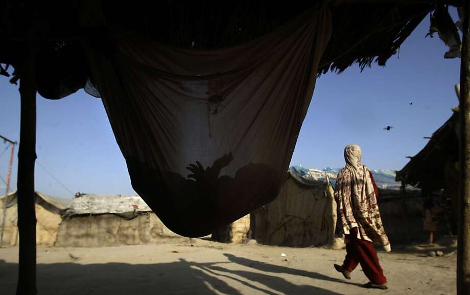 A Pakistani child whose family was displaced by 2010 floods from a village near Multan, sleeps in a hammock attached to his family's makeshift tent, in a slum on the outskirts of Islamabad, Pakistan, Monday, May 14, 2012. (AP Photo/Muhammed Muheisen) Photo: Muhammed Muheisen, Associated Press
