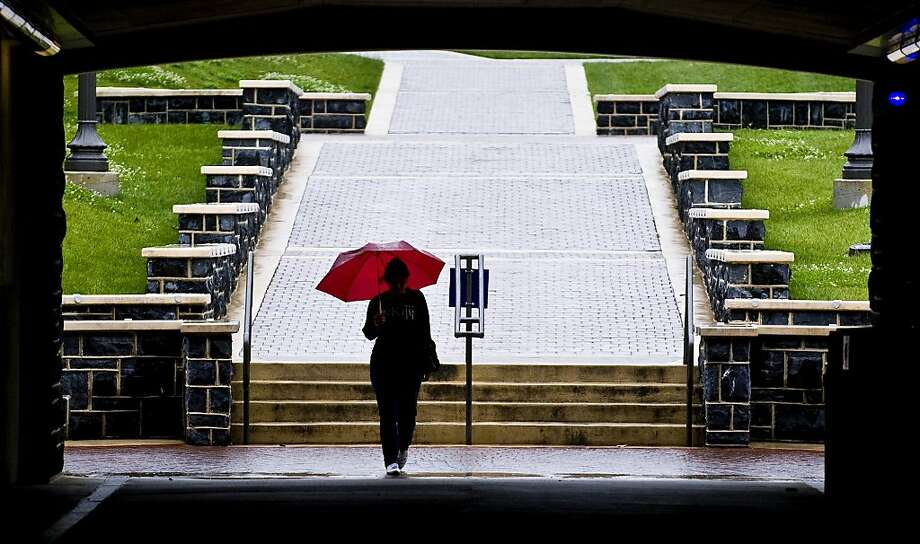 A student carrying an umbrella heads into the tunnel under S. Main Street towards James Madison University's Fine Arts Center in Harrisonburg, Va., Monday, May 14, 2012. (AP Photo/Daily News-Record, Justin Falls) Photo: Justin Falls, Associated Press