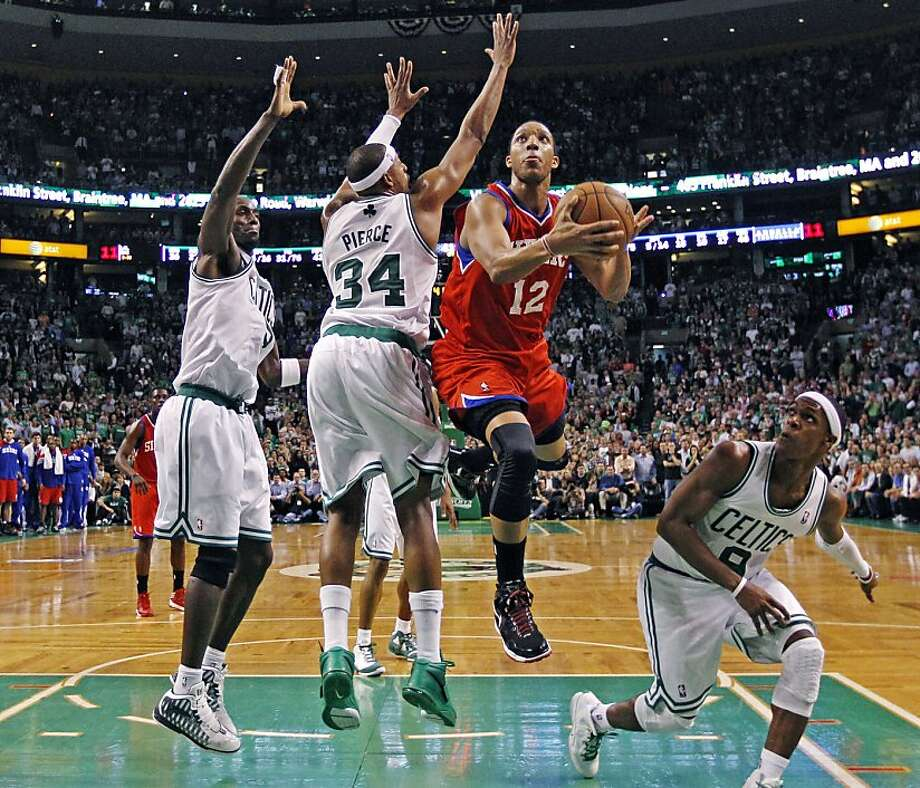 Philadelphia 76ers shooting guard Evan Turner (12) gets past Boston Celtics forward Kevin Garnett, left, small forward Paul Pierce (34), and guard Rajon Rondo to score the go-ahead basket in the final minute of the second half of Game 2 in their NBA basketball Eastern Conference semifinal playoff series in Boston, Monday, May 14, 2012. The 76ers won 82-81. (AP Photo/Charles Krupa) Photo: Charles Krupa, Associated Press