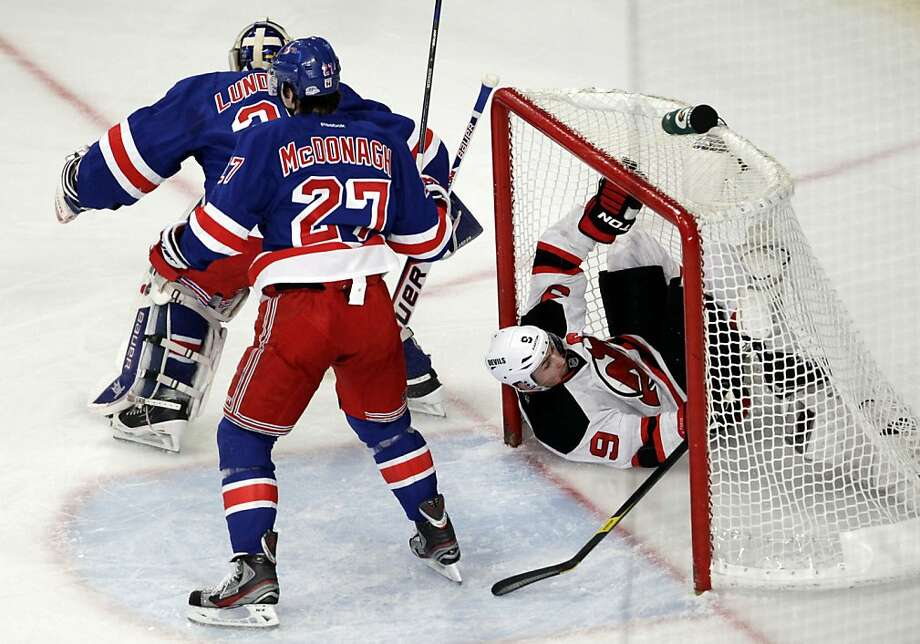 New Jersey Devils' Zach Parise, right, goes into the net after his shot was deflected by New York Rangers goalie Henrik Lundqvist, rear, of Sweden, and Ryan McDonagh (27) during the first period of Game 1 of their NHL hockey Stanley Cup Eastern Conference final playoff series, Monday, May 14, 2012, at New York's Madison Square Garden. (AP Photo/Julio Cortez) Photo: Julio Cortez, Associated Press