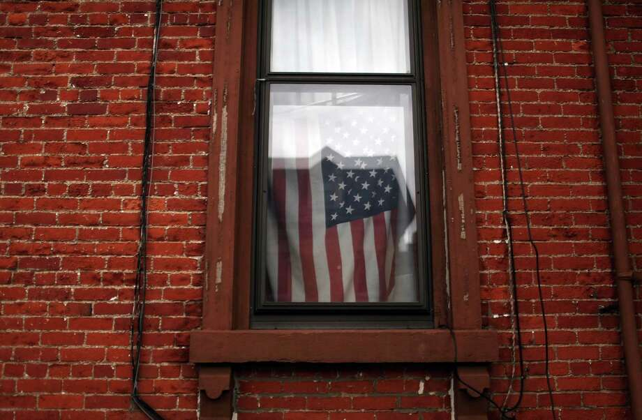 UTICA, NY - MAY 14: A flag hangs in a window on May 14, 2012 in Utica, New York. Like many upstate New York communities, Utica is struggling to make the transition from a former manufacturing hub. The city's individual poverty rate is twice the national average with an unemployment rate of 9.8% as of February 2012. Citing Utica's weakening financial margins over the past two years, Fitch Ratings downgraded its credit rating on Utica by two notches to a triple-B, two rungs above junk territory. Photo: Spencer Platt, Getty Images / 2012 Getty Images