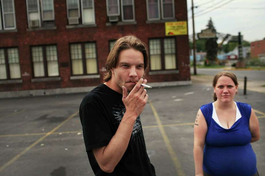 UTICA, NY - MAY 14: Unemployed couple Tiffany Drake and Mike Johnson stand on a Utica street corner on May 14, 2012 in Utica, New York. Like many upstate New York communities, Utica is struggling to make the transition from a former manufacturing hub. The city's individual poverty rate is twice the national average with an unemployment rate of 9.8% as of February 2012. Citing Utica's weakening financial margins over the past two years, Fitch Ratings downgraded its credit rating on Utica by two notches to a triple-B, two rungs above junk territory. Photo: Spencer Platt, Getty Images / 2012 Getty Images