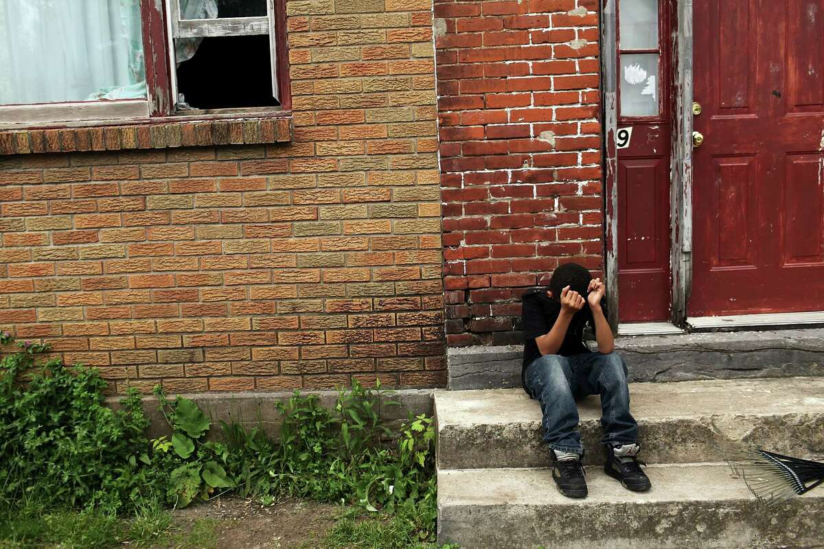 UTICA, NY - MAY 14: A child sits on a stoop in a working class section of Utica on May 14, 2012 in Utica, New York. Like many upstate New York communities, Utica is struggling to make the transition from a former manufacturing hub. The city's individual poverty rate is twice the national average with an unemployment rate of 9.8% as of February 2012. Citing Utica's weakening financial margins over the past two years, Fitch Ratings downgraded its credit rating on Utica by two notches to a triple-B, two rungs above junk territory.