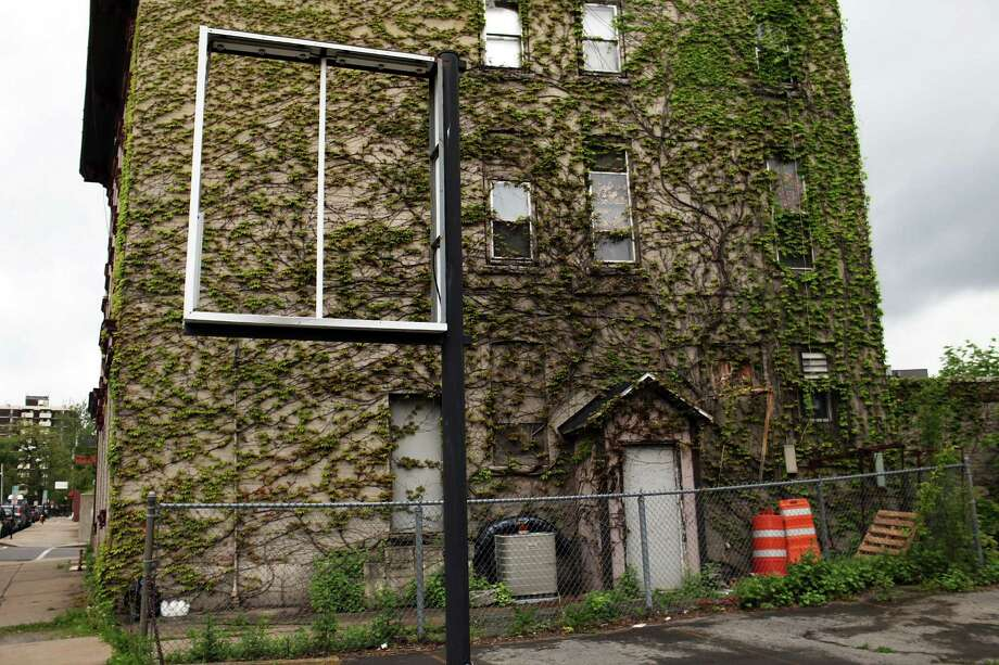 UTICA, NY - MAY 14:  A building is covered in ivy on May 14, 2012 in Utica, New York. Like many upstate New York communities, Utica is struggling to make the transition from a former manufacturing hub. The city's individual poverty rate is twice the national average with an unemployment rate of 9.8% as of February 2012. Citing Utica's weakening financial margins over the past two years, Fitch Ratings downgraded its credit rating on Utica by two notches to a triple-B, two rungs above junk territory. Photo: Spencer Platt, Getty Images / 2012 Getty Images
