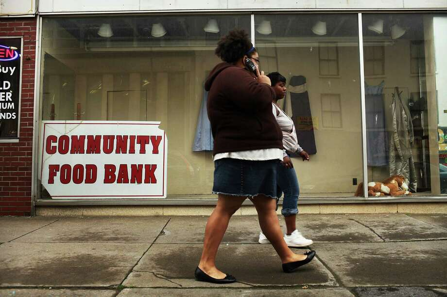 UTICA, NY - MAY 14: Women walk by a food bank on May 14, 2012 in Utica, New York. Like many upstate New York communities, Utica is struggling to make the transition from a former manufacturing hub. The city's individual poverty rate is twice the national average with an unemployment rate of 9.8% as of February 2012. Citing Utica's weakening financial margins over the past two years, Fitch Ratings downgraded its credit rating on Utica by two notches to a triple-B, two rungs above junk territory. Photo: Spencer Platt, Getty Images / 2012 Getty Images