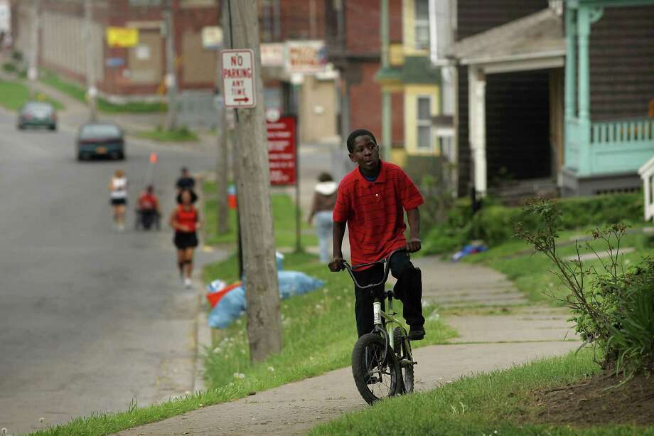 UTICA, NY - MAY 14:  A child rides his bike in downtown Utica on May 14, 2012 in Utica, New York. Like many upstate New York communities, Utica is struggling to make the transition from a former manufacturing hub. The city's individual poverty rate is twice the national average with an unemployment rate of 9.8% as of February 2012. Citing Utica's weakening financial margins over the past two years, Fitch Ratings downgraded its credit rating on Utica by two notches to a triple-B, two rungs above junk territory. Photo: Spencer Platt, Getty Images / 2012 Getty Images