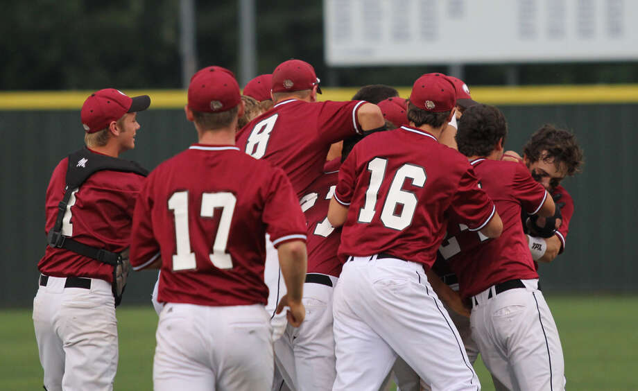 Jasper's players mob Joe Walker after his hit drove in the winning run against Madisonville. Photo: Jason Dunn