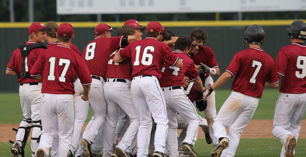 Joe Walker is mobbed by his teammates after driving in the winning run Saturday. Photo: Jason Dunn