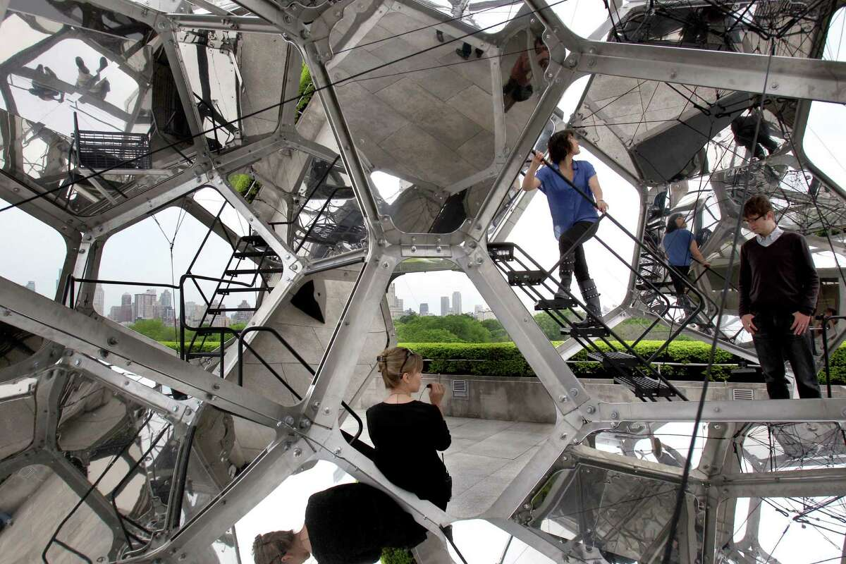 Visitors look at a structure by Tomas Saraceno called