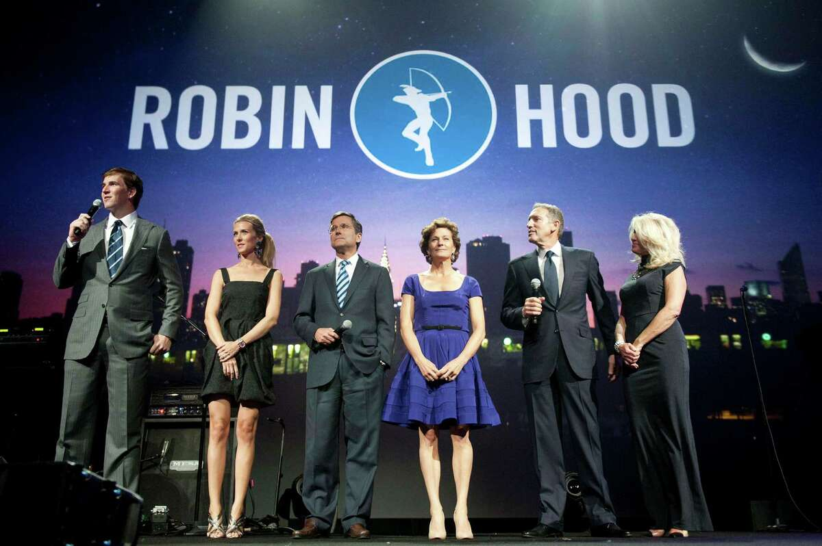 In this photo provided by Robin Hood, Robin Hood Benefit event co-chairs, from left, New York Giants NFL football quarterback Eli Manning, Abby Manning, Steve Burke, Gretchen Burke, Howard Schultz and Sheri Schultz appear onstage at the Robin Hood Annual Benefit, Monday, May 14, 2012, at the Javits Center in New York. Robin Hood funds programs that fight poverty in New York City.