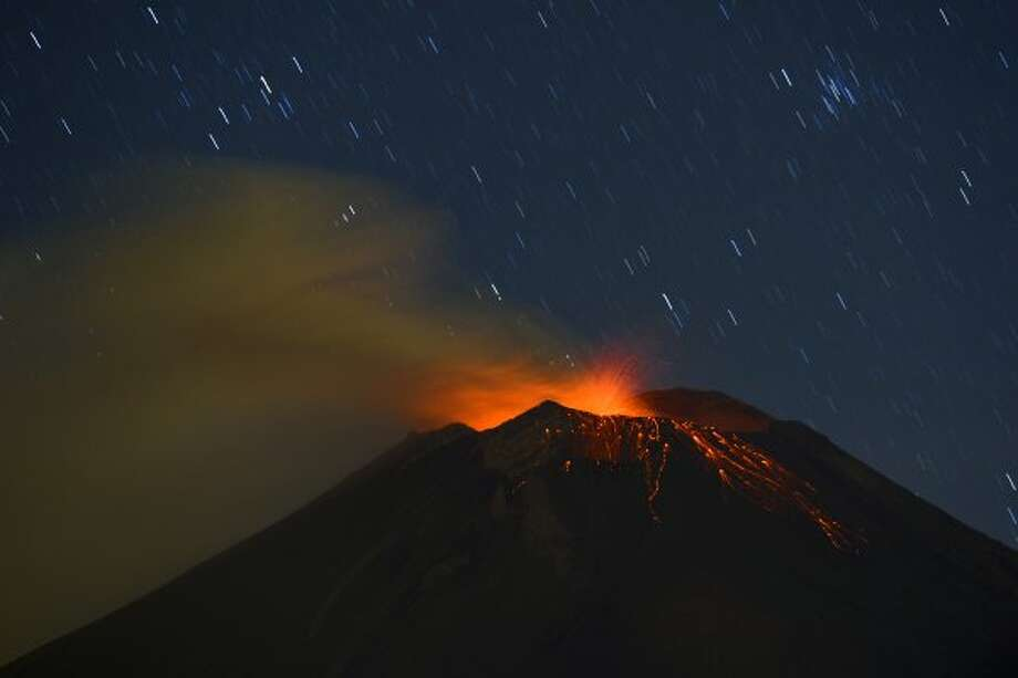 Incandescent materials, ash and smoke are spewed from the Popocatepetl Volcano as seen from Santiago Xalitzintla, in the Mexican central state of Puebla, on April 24, 2012. Residents at the foot of Mexico's Popocatepetl volcano no longer sleep soundly since the towering mountain roared back into action over a week ago, spewing out a hail of rocks, steam and ashes. The volcano, Mexico's second highest peak at 5,452 metres, started rumbling and spurting high clouds of ash and steam on April 13, provoking the authorities to raise the alert to level five on a seven-point scale. AFP PHOTO//RONALDO SCHEMIDT (Photo credit should read Ronaldo Schemidt/AFP/Getty Images) (AFP/Getty Images)