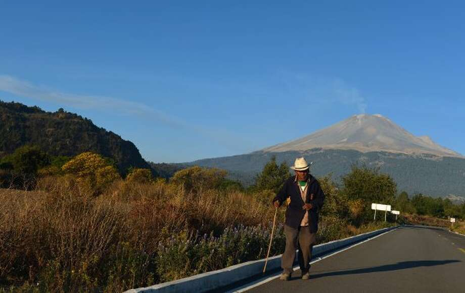An old man walks in a road with the Popocatepetl volcano at the back, in Paso de Cortes, in the Mexican central state of Puebla, on April 28, 2012. The volcano, Mexico's second highest peak at 5,452 metres, started rumbling and spurting high clouds of ash and steam on April 13, provoking the authorities to raise the alert to level five on a seven-point scale.   AFP PHOTO/Yuri CORTEZ        (Photo credit should read YURI CORTEZ/AFP/GettyImages) (AFP/Getty Images)