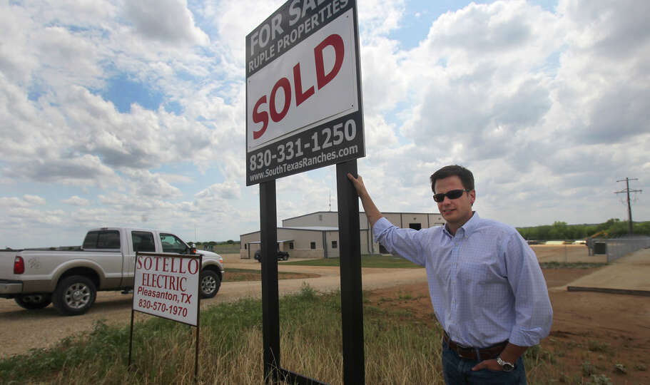 Garrett Ruple stands next to some commercial property recently sold on Interstate 37 near Pleasanton