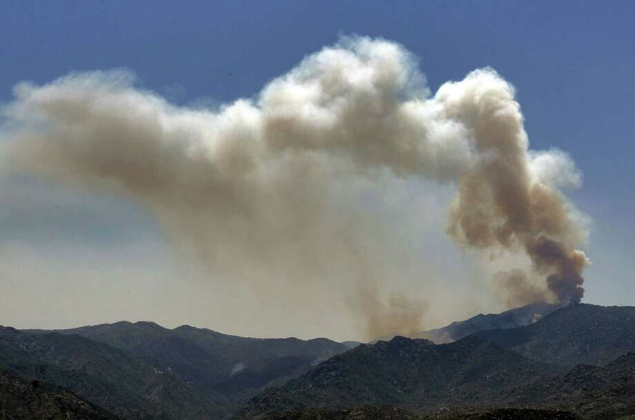 A smoke column rises near Crown King, Ariz. Fire crews spent the weekend fighting several wildfires including the four and a half square mile blaze near Crown King. Photo: AP
