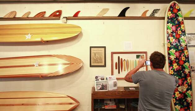 Marco Garza, of Corpus Christi makes a picture of the Texas Surf Museums surf board evolution exhibit, Saturday, March 24, 2012, in Corpus Christi. Photo: Nick De La Torre, Staff / © 2012  Houston Chronicle