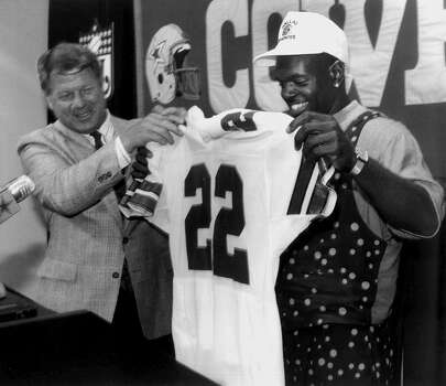 ** FILE ** Former Dallas Cowboys head coach Jimmy Johnson, left, hands Florida running back Emmitt Smith his No. 22 jersey as the Cowboys 1990 No. 1 draft pick is  introduced at the Cowboys training facility in Irving, Texas, in this April 22, 1990 file photo. NFL career rushing leader Emmitt Smith is retiring after 15 years, two sources within the NFL said. Smith, who starred for the Dallas Cowboys for 13 seasons and spent the last two years with Arizona, will make the announcement in the afternoon at the site of the Super Bowl, according to the sources, who spoke to The Associated Press on condition of anonymity. (AP Photo/David J. Sams) Photo: DAVID J. SAMS, STR / Beaumont