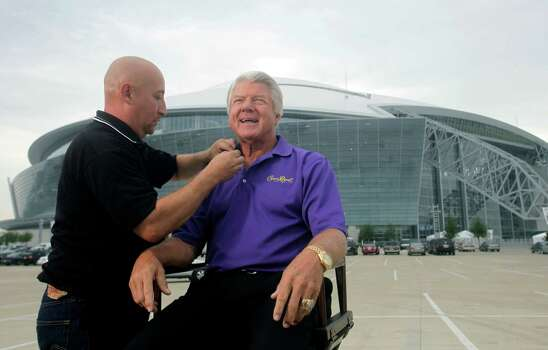 Former Dallas Cowboys head football coach Jimmy Johnson, right, get wired with a microphone by Larry Rodriguez before filming a commercial outside Cowboys Stadium in Arlington,  Texas, Thursday, Aug. 27, 2009.  (AP Photo/LM Otero) Photo: LM Otero, STF / AP
