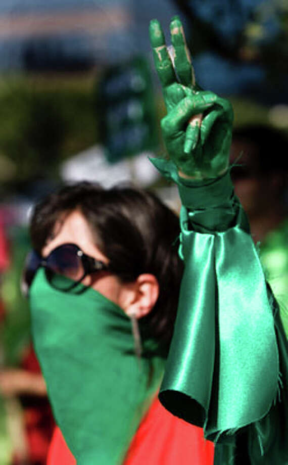 A woman, who identified herself only as Gelareh, holds up her hand, painted gree, as she protests the election results in Iran at the corner of Westheimer and Post Oak Tuesday, June 16, 2009, in Houston.  ( Brett Coomer / Chronicle ) (Houston Chronicle)