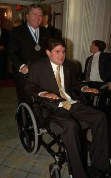 """Former Dallas Cowboys coach and current NFL analyst Jimmy Johnson and Marc Buoniconti make their entrance at the reception for the ninth annual """"Great Sports Legends"""" benefit dinner at New York's Waldorf-Astoria Hotel, Oct. 4, 1994.  Eleven of the greatest names in sports were honored at th dinner to benefit the Buoniconti Fund to cure Paralysis.  Marc Buoniniconti, son of former Miami Dolphins All-Pro linebacker Nick Buoniconit was injured during a college football qame in October 1985. He is now a quadriplegic. (AP photo/Ron Frehm) Photo: RON FREHM, STF / AP1994"""