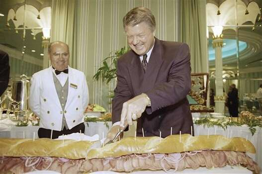 Dallas Cowboys Coach Jimmy Johnson cuts a large sandwich following a press conference where he announced plans for Jimmy Johnson?s Three Rings Bar and Grill to open at the Eden Roc Resort and Spa in Miami Beach, Florida on Thursday, Nov. 3, 1994. The tongue and baloney sandwich was named the Barry and Jerry sandwich after Cowboys Coach Barry Switzer and Cowboys owner Jerry Jones. The restaurant is scheduled to open on January 17, 1995 in time for Super Bowl week in Miami. (AP Photo) / AP1994