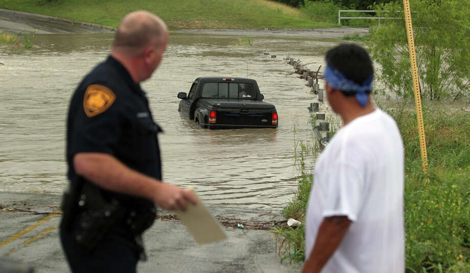 San Antonio police officer Scott Knirlberger (left) hands a citation over to Lorenzo Gutierrez (right) after Gutierrez drove his Ford pickup into high water on May 15, 2012 on Vicar street near Perrin Beitel. Gutierrez said he came around the corner and saw the water, slammed on his brakes and slowly slid into the water. After trying to drive out, Gutierrez ended up abandoning the vehicle. Photo: John Davenport/Express-News
