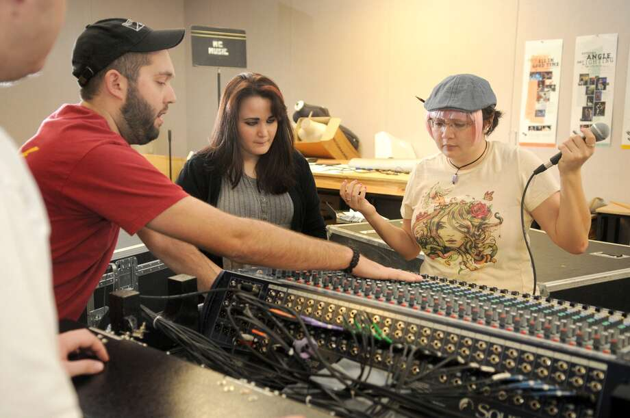 Chris Krumins, from left, adjunct professor of live entertainment technology at Lone Star College-Montgomery, instructs class members Charlee Kristof and Caroline Mckay during a lab session. Photo: Jerry Baker