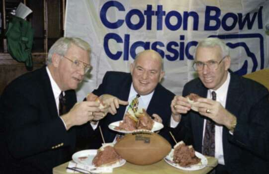 "Texas A & M Athletic Director John David Crow, left, and head football coach R.C. Slocum, right, join Jim ""Hoss"" Brock, executive vice president of the Mobil Cotton Bowl for lunch at New York's Carnegie Deli, Monday, Dec. 14, 1992. The Aggies will face the Fighting Irish of Notre Dame in the Mobil Cotton Bowl on January 1. (AP Photo/Teddy Blackburn) Photo: Teddy Blackburn, STR / AP1992"
