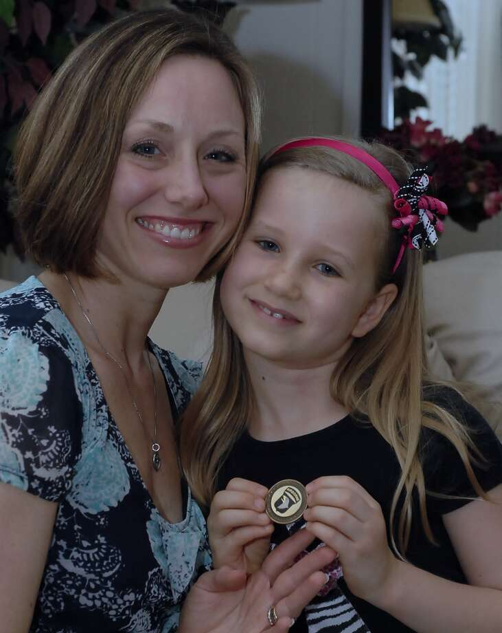 Stacie Ripkowski checks out the medallion given to her daughter Abigail by a PTSD Foundation of America veteran. Abigail is raising money for the foundation. Photo: Tony Bullard / Tony Bullard & the Houston Chronicle