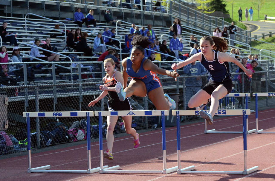 Staples' Emily Troelstra, right, competes in the 110-meter hurdles April 30 against Danbury and Ridgefield. On Monday, Troelstra won the 110-hurdles and three other events in the Lady Wreckers' tri-meet sweep of Norwalk and Stamford. Photo: Amy Mortensen, Amy Mortensen / For The Westport News / Connecticut Post Freelance