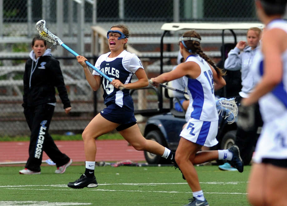 Staples' Ali Crofts, left, tries to elude Fairfield Ludlowe defenders May 8. On Thursday, Crofts had two goals, one assist, three draw controls, three ground balls and a caused turnover in a 15-11 win at Danbury. Photo: Christian Abraham, Christian Abraham/Staff Photographer / Connecticut Post