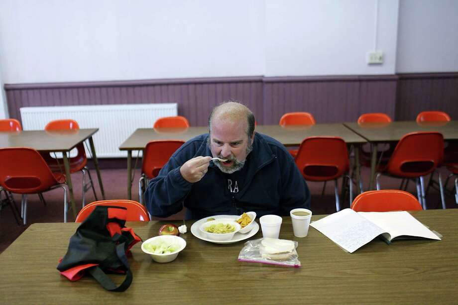 UTICA, NY - MAY 15: Mike Patterson, who is currenlty without employment, eats lunch at Mother Marianne's West Side Soup Kitchen on May 15, 2012 in Utica, New York. Like many upstate New York communities, Utica is struggling to make the transition from a former manufacturing hub. The city's individual poverty rate is twice the national average with an unemployment rate of 9.8 percent as of February 2012. Citing Utica's weakening financial margins over the past two years, Fitch Ratings downgraded its credit rating on Utica by two notches to a triple-B, two rungs above junk territory. Photo: Spencer Platt, Getty Images / 2012 Getty Images