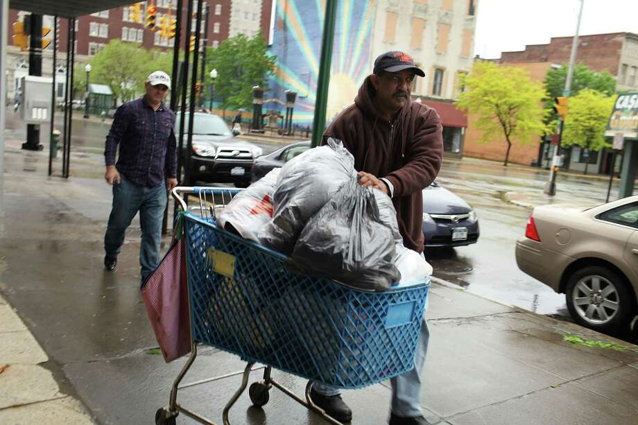 UTICA, NY - MAY 15: Eugenid Vasquez brings in clothing donations into a local food bank on May 15, 2012 in Utica, New York. Like many upstate New York communities, Utica is struggling to make the transition from a former manufacturing hub. The city's individual poverty rate is twice the national average with an unemployment rate of 9.8 percent as of February 2012. Citing Utica's weakening financial margins over the past two years, Fitch Ratings downgraded its credit rating on Utica by two notches to a triple-B, two rungs above junk territory. Photo: Spencer Platt, Getty Images / 2012 Getty Images
