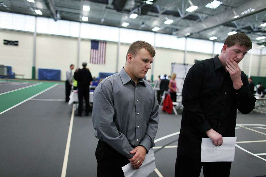 UTICA, NY - MAY 15: Veterans Kris Hummel (left) and Shane Foley, both of whom currently do not have work, speak with a representative from a company at the Hiring Our Heroes Veterans/Military job fair on May 15, 2012 in Utica, New York. Like many upstate New York communities, Utica is struggling to make the transition from a former manufacturing hub. The city's individual poverty rate is twice the national average with an unemployment rate of 9.8 percent as of February 2012. Citing Utica's weakening financial margins over the past two years, Fitch Ratings downgraded its credit rating on Utica by two notches to a triple-B, two rungs above junk territory. Photo: Spencer Platt, Getty Images / 2012 Getty Images