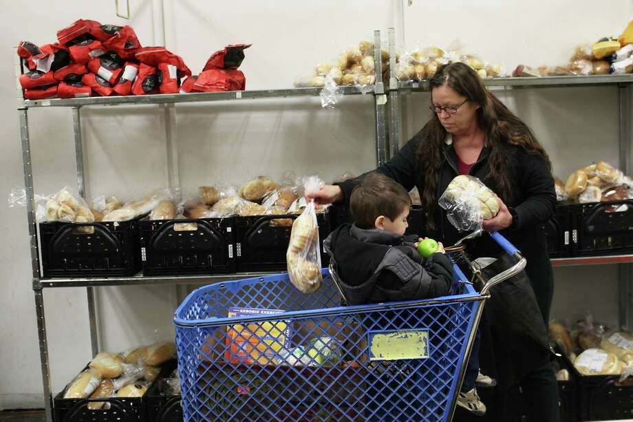UTICA, NY - MAY 15:  Meagan Stokey picks up food with her grandson at a food bank on May 15, 2012 in Utica, New York. Like many upstate New York communities, Utica is struggling to make the transition from a former manufacturing hub. The city's individual poverty rate is twice the national average with an unemployment rate of 9.8 percent as of February 2012. Citing Utica's weakening financial margins over the past two years, Fitch Ratings downgraded its credit rating on Utica by two notches to a triple-B, two rungs above junk territory. Photo: Spencer Platt, Getty Images / 2012 Getty Images