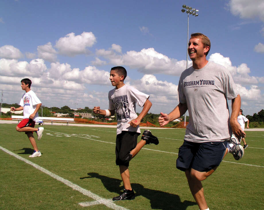 NFL quarterback Ty Detmer, who attended Southwest High School and earned a Heisman Trophy while quarterbacking Brigham Younng University, runs a warm-up exercise with students at the Ty & Koy Detmer Football Camp at Cornerstone Christian School on Wednesday, July 7, 2004. The camp runs through Friday and students are still being accepted. BILLY CALZADA / STAFF Photo: BILLY CALZADA, Express-News / SAN ANTONIO EXPRESS-NEWS