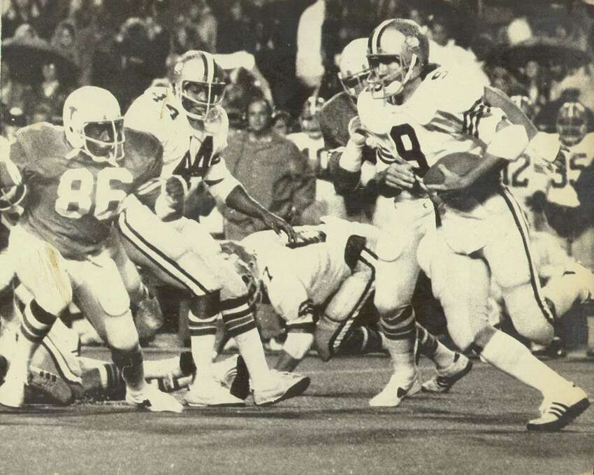 Rice quarterback Tommy Krame (9) does some fancy stepping as he picks up an eight-ard gain in the first quarter with Texas at Austin. At left is defensive end Tim Campbell (86) of Texas and John Coleman (44) of Rice.
