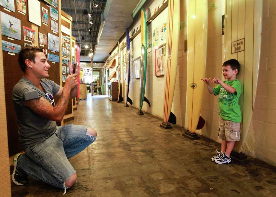 Marco Garza, of Corpus Christi, left, takes a picture of his son Kane Garza, 4, as they visit the Texas Surf Museum, Saturday, March 24, 2012, in Corpus Christi. Photo: Nick De La Torre, Houston Chronicle / © 2012  Houston Chronicle