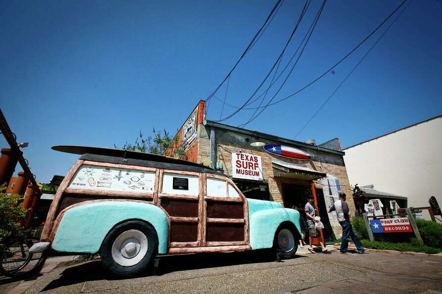 Visitors leave the Texas Surf Museum, which has a sculpture of a Woody automobile out front, Saturda