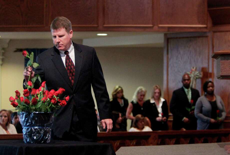 Special Agent Bobby Martin places a rose for his friend Special Agent Jerry Dove in the Roll Call of Martyrs during the FBI Law Enforcement Memorial Service at Our Savior Lutheran Church on Tuesday, May 15, 2012, in Houston.  Special Agent Jerry Dove was killed in southwest Miami, Florida, during a gun battle with robbery suspects on April 11, 1986. Photo: Mayra Beltran, Houston Chronicle / Houston Chronicle