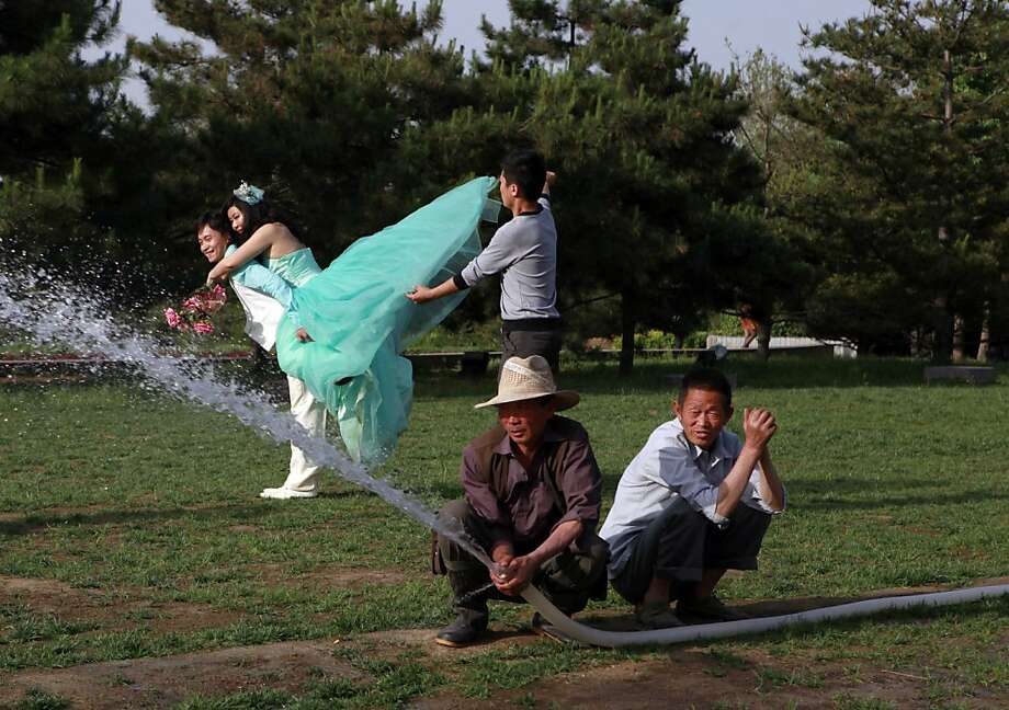 Crouching gardeners, lunging bride: Park workers watering a lawn pay no attention as wedding shoot gets creative in Beijing. Photo: Ng Han Guan, Associated Press