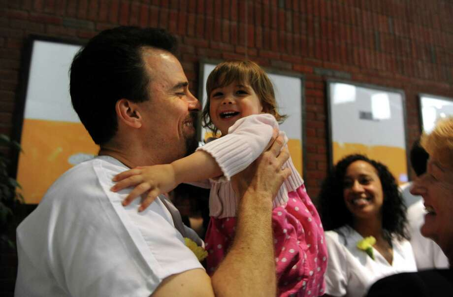 Graduate Nicholas Molnar gets a hug from his 21-month-old daughter, Sabina, during the Nursing Class of 2012 Pinning Ceremony Tuesday, May 15, 2012 at Norwalk Community College. Photo: Autumn Driscoll / Connecticut Post